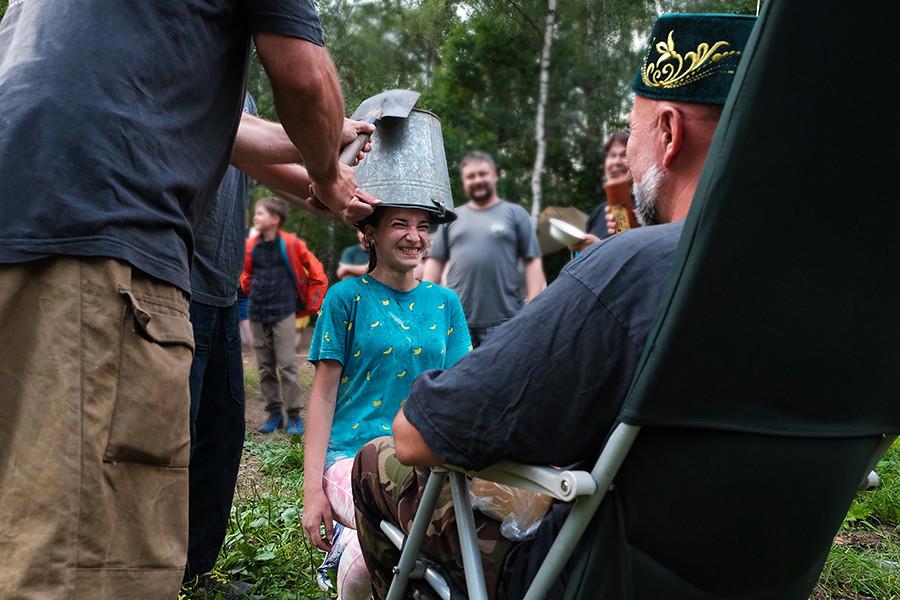 Na expedição, o golpe de uma pá em um balde vazio na cabeça finaliza a iniciação. Sentado, está o 'cã'.