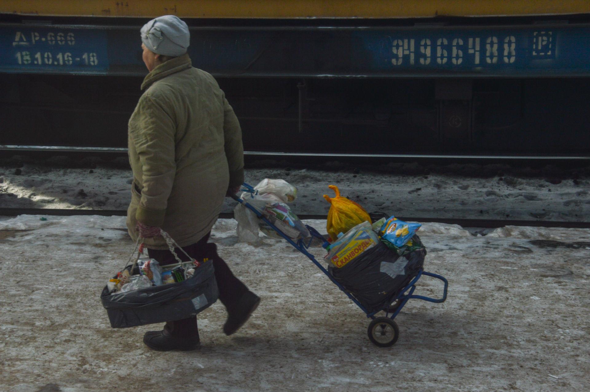 Una babushka si prepara a vendere la sua merce ai passeggeri del prossimo treno