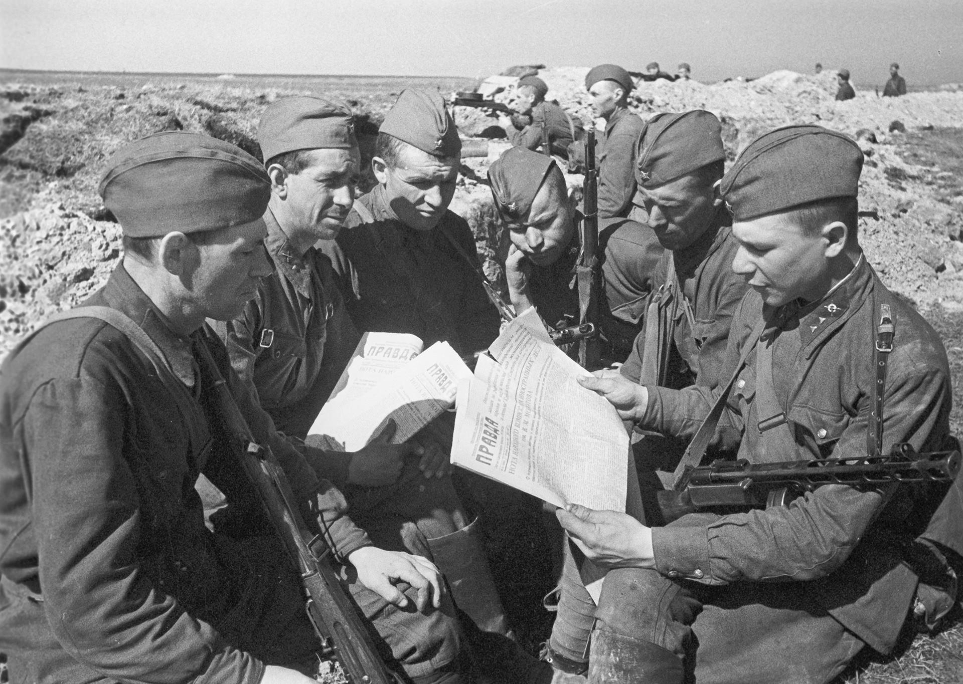 """Црвеноармејци у рововима Лењинградског фронта читају лист """"Правда"""", 1942."""