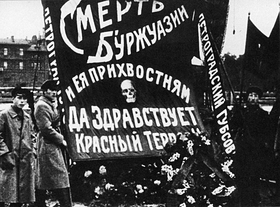 モイセイ・ウリツキーの墓のそばにいる管理人たち。ペトログラード。ポスターには「ブルジョワおよびその支援者を殺せ!赤色テロ、万歳!」と書いてある。