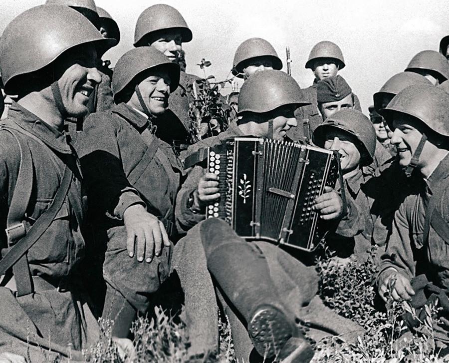 U trenucima predaha vojnici slušaju suborca harmonikaša Pantahova