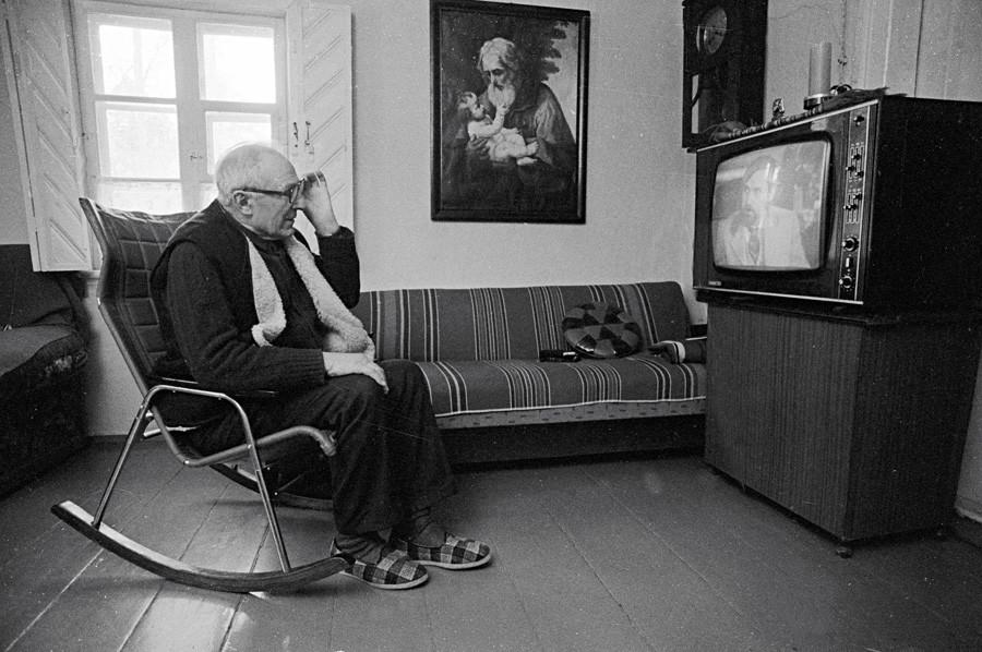 男性がロッキングチェアに座ってテレビを見ている。