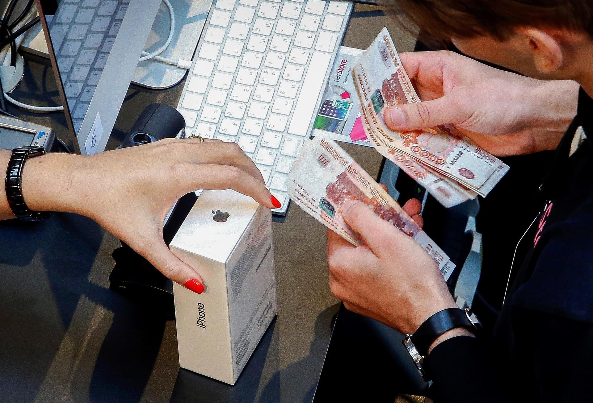 デパート「グム」で新しいiPhone 7の発売の時に店を訪れた客。ショップアシスタントはルーブル札を数えている。