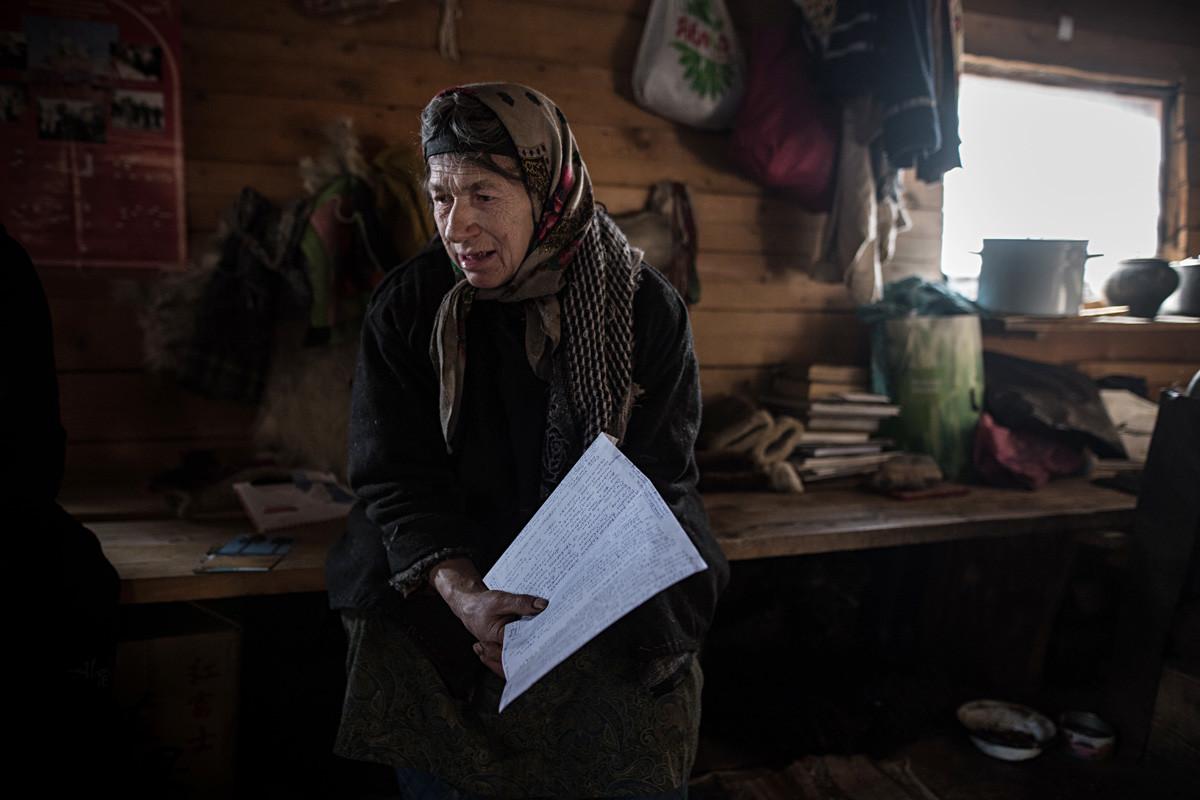 Agafia Lykova reads a letter form Bolivia