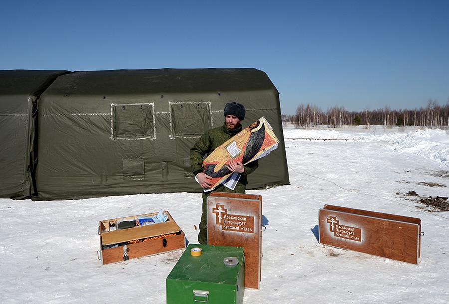 Seorang pendeta di dekat gereja bergerak yang didirikan di tempat pendaratan, selama latihan pelatihan udara di lapangan bagi pendeta militer di Oblast Ryazan.