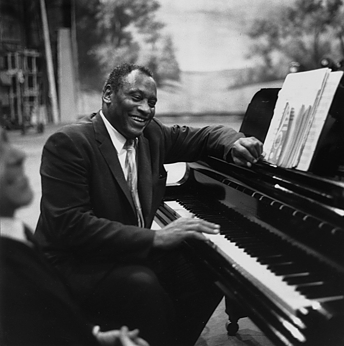 22nd July 1958: American singer, acclaimed actor of stage and screen, political activist and civil rights campaigner Paul Robeson (1898 - 1976), rehearses in relaxed mood at the piano