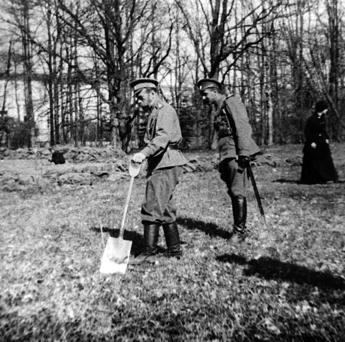 Emperor Nicholas II of Russia (L) holds a shovel while being under a house arrest in Tsarskoye Selo