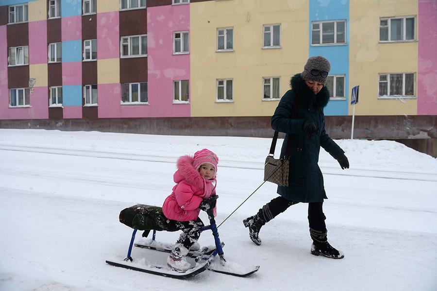 Seorang wanita dengan seorang anak di jalanan Anadyr. November 2013.