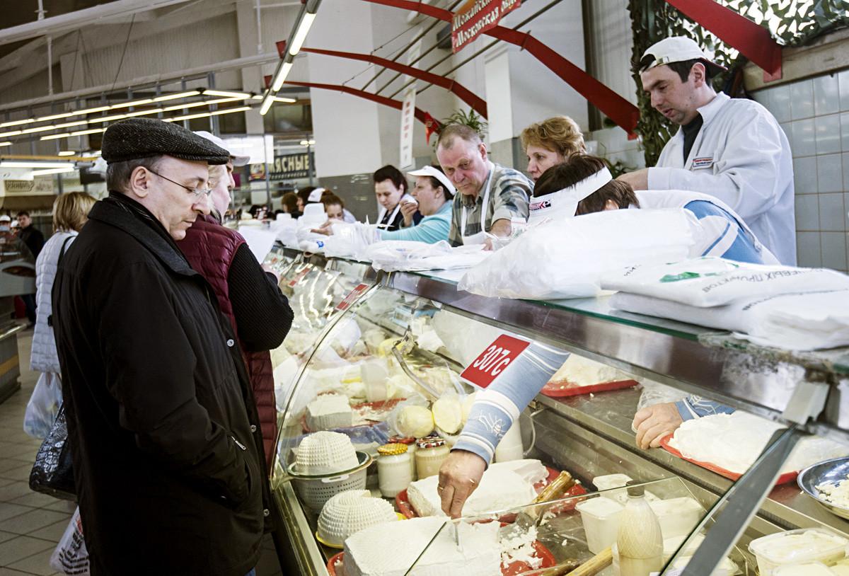 モスクワのドロゴミロフスキー市場にある乳製品コーナーの客と店員。