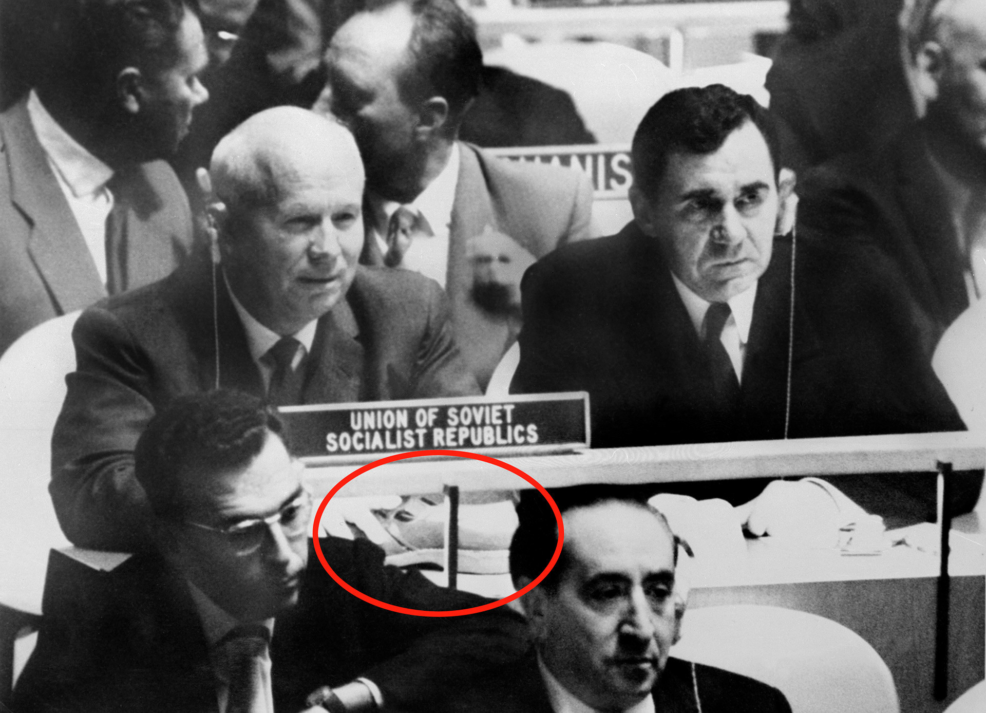 Foto verdadeira de Khruschov com o ministro dos Negócios Estrangeiros soviético Andrêi Gromiko (dir.) na Assembleia da ONU; círculo vermelho destaca sapato do líder soviético sobre a mesa