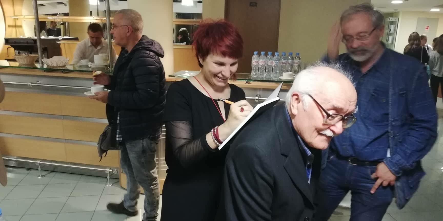Ирина Антанасијевић потписује своју књигу посвећену Јурију Лобачову на леђима његовог потомка Дмитрија Лобачова.