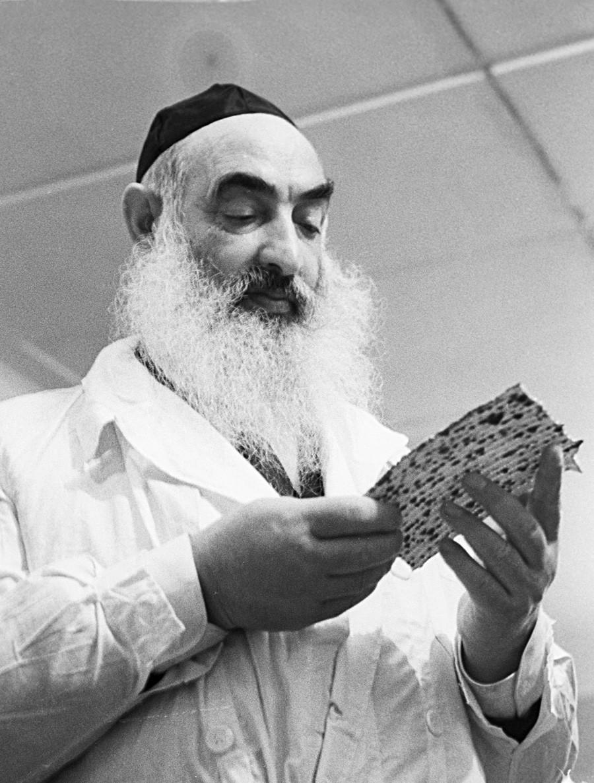 Rabbi Yehuda Leib Levin memeriksa matzoh buatan pabrik. 1968, Moskow.