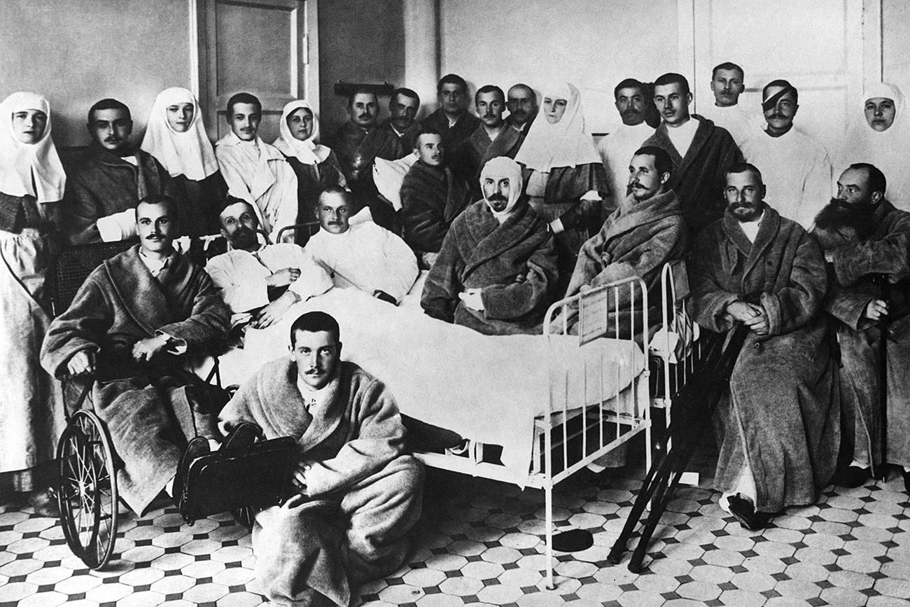 Ruska carica Aleksandra Fjodorovna in njene hčerke med ranjenimi vojaki v bolnišnici v Carskem Selu.