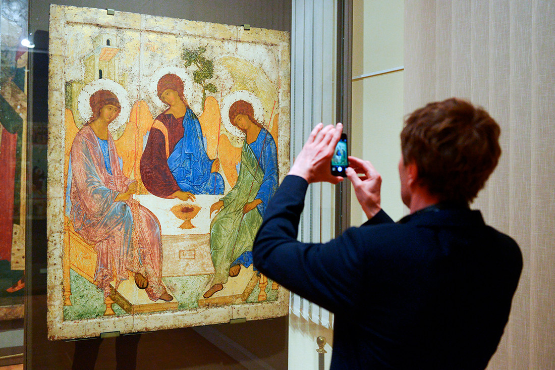 A young man taking photo of Andrei Rublev's Icon of the Holy Trinity (1425–1427) at the Tretyakov State Gallery.