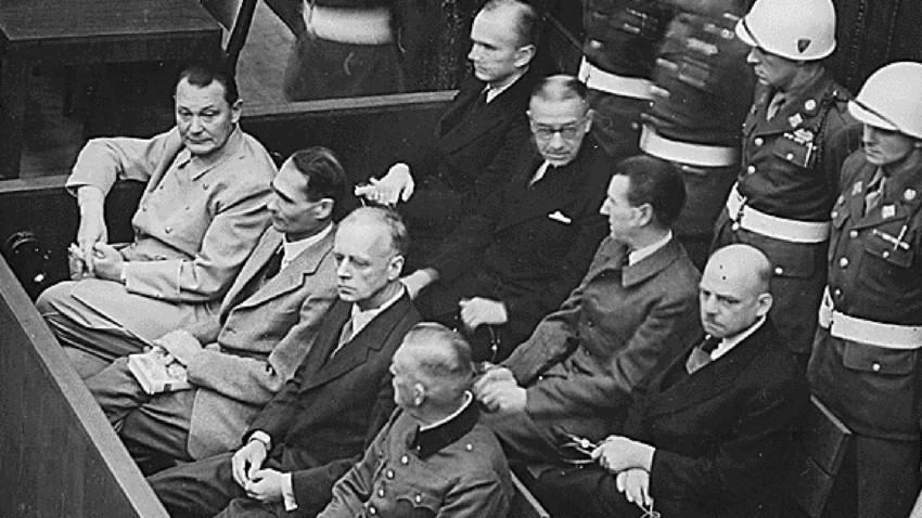 Оптужени нацисти (први ред слева надесно) Херман  Геринг, Рудолф Хес, Јоаким фон Рибентроп и Вилхелм Кајтел на суду за ратне злочине у Нирнбергу 1945-1946. године.