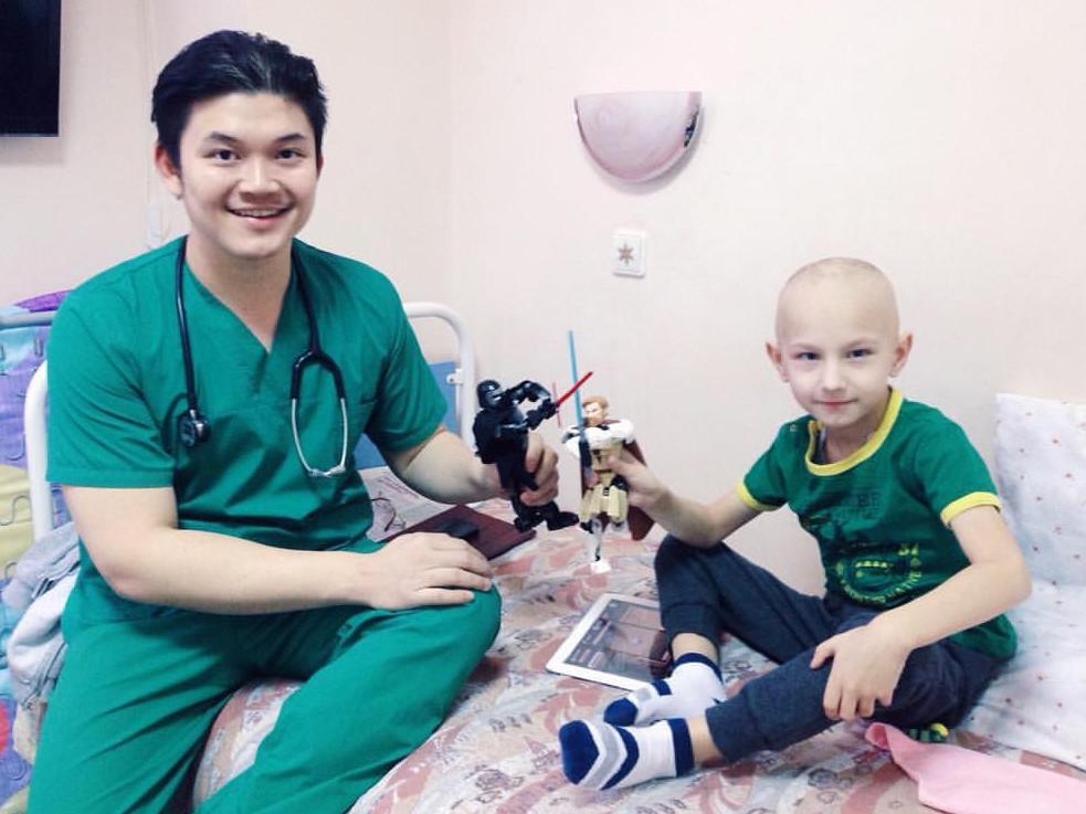 Steven Guntur bermain dengan seorang pasien yang akan menjalani kemoterapi di Rumah Sakit Anak Pemerintah di Sankt Petersburg.