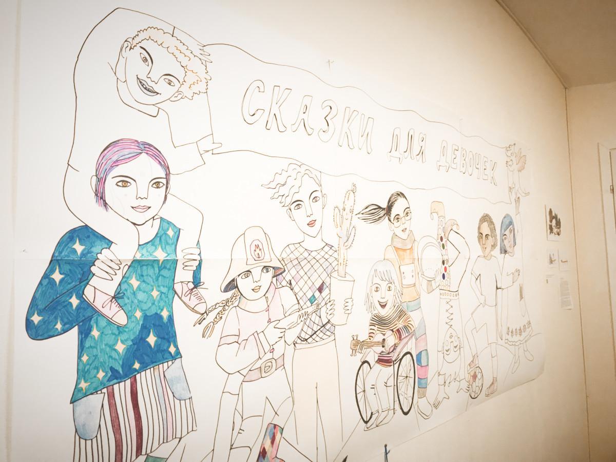 """Ilustração do livro """"Contos de fadas para meninas"""" na parede."""