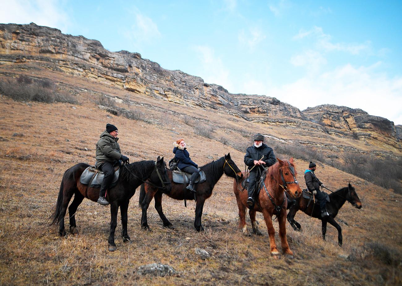 クラースヌィ・クルガン村で乗馬クラブ「グン」の馬に乗っている観光客。
