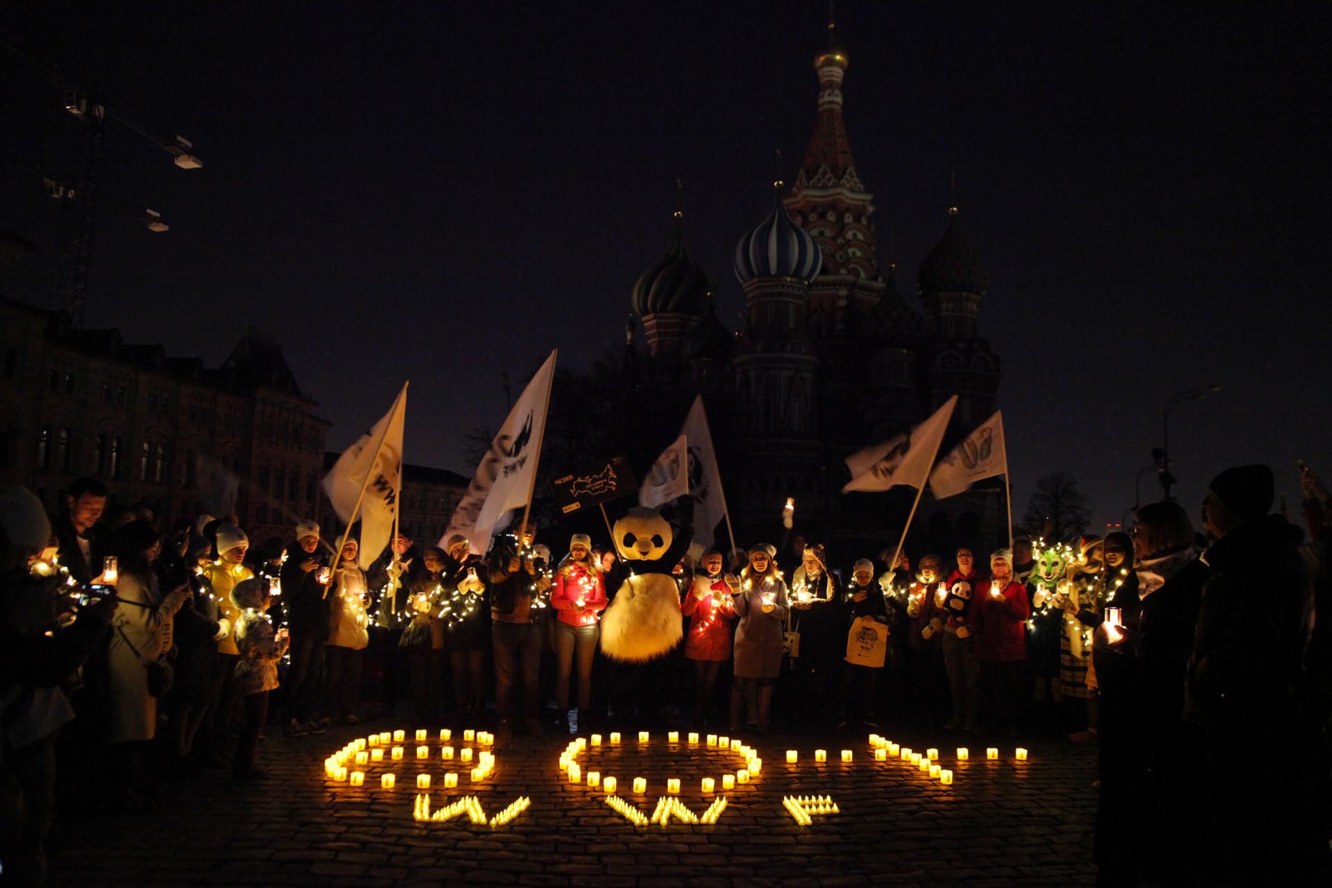 Aktivis dan masyarakat melakukan aksi Earth Hour di depan Katedral Saint Basil saat berlangsung pemadaman lampu.