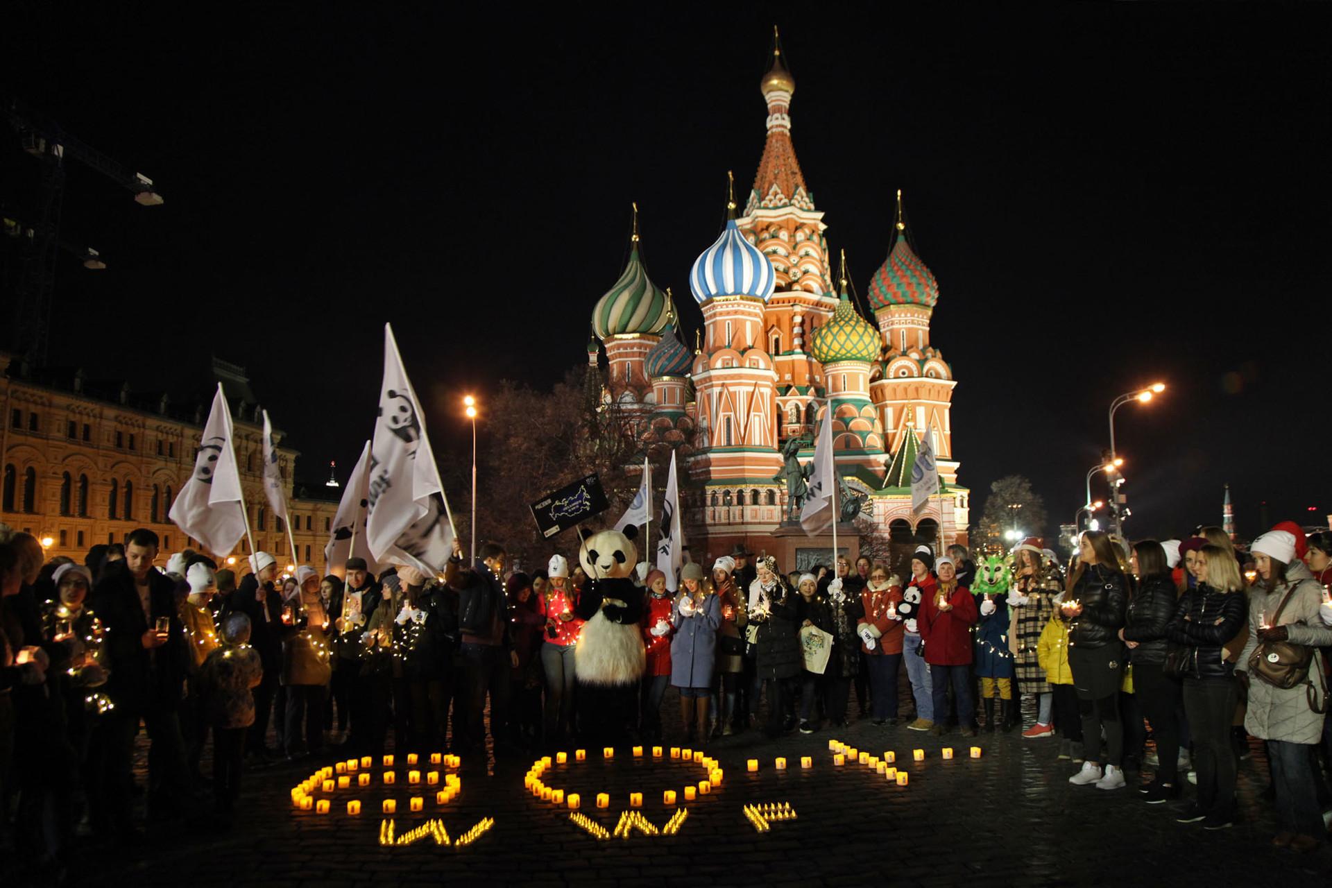 Aktivis dan masyarakat melakukan aksi Earth Hour di depan Katedral Saint Basil sebelum pemadaman lampu.
