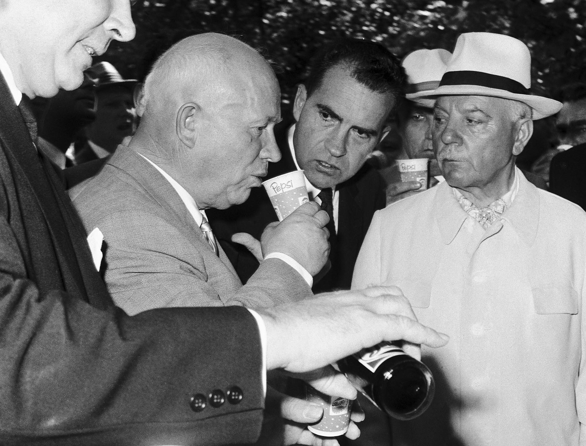 """Москва, Советскиот Сојуз. Советскиот премиер Никита Хрушчов испива Пепси кола под будното око на претседателот на САД Ричард Никсон (во центарот) и претседателот на СССР Климент Ворошилов (десно) во паркот """"Сокољники"""" на 24 јули 1959 година."""