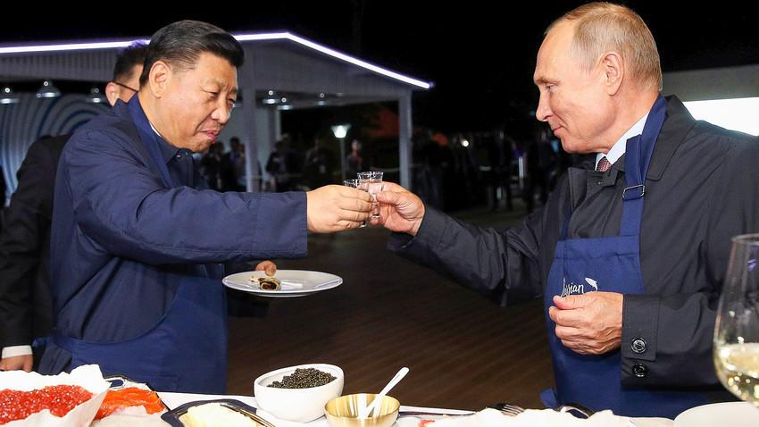 Vladimir Putin dan Xi Jinping mencoba makanan Rusia dalam acara Eastern Economic Forum pada 2018.