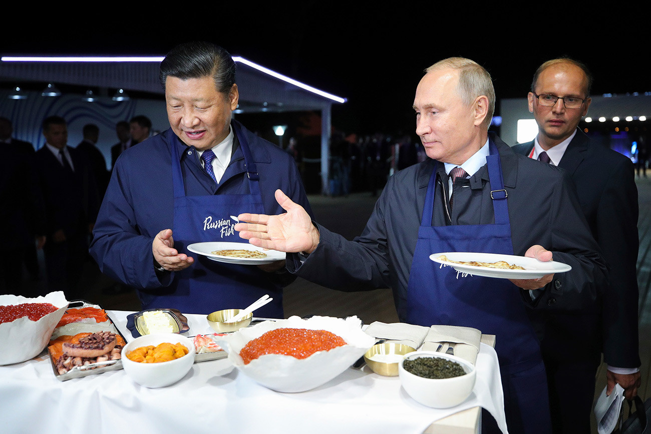 Vladimir Putin and Xi Jinping trying Russian food at the Eastern Economic Forum in 2018