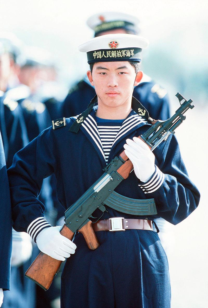 Un oficial chino con un AK-56 en las manos.