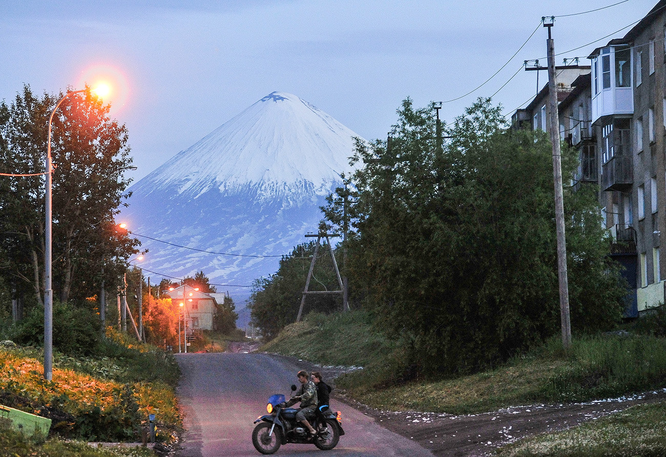 Residents of Klyuchy village in Kamchatka. Background: Klyuchevskaya Sopka.
