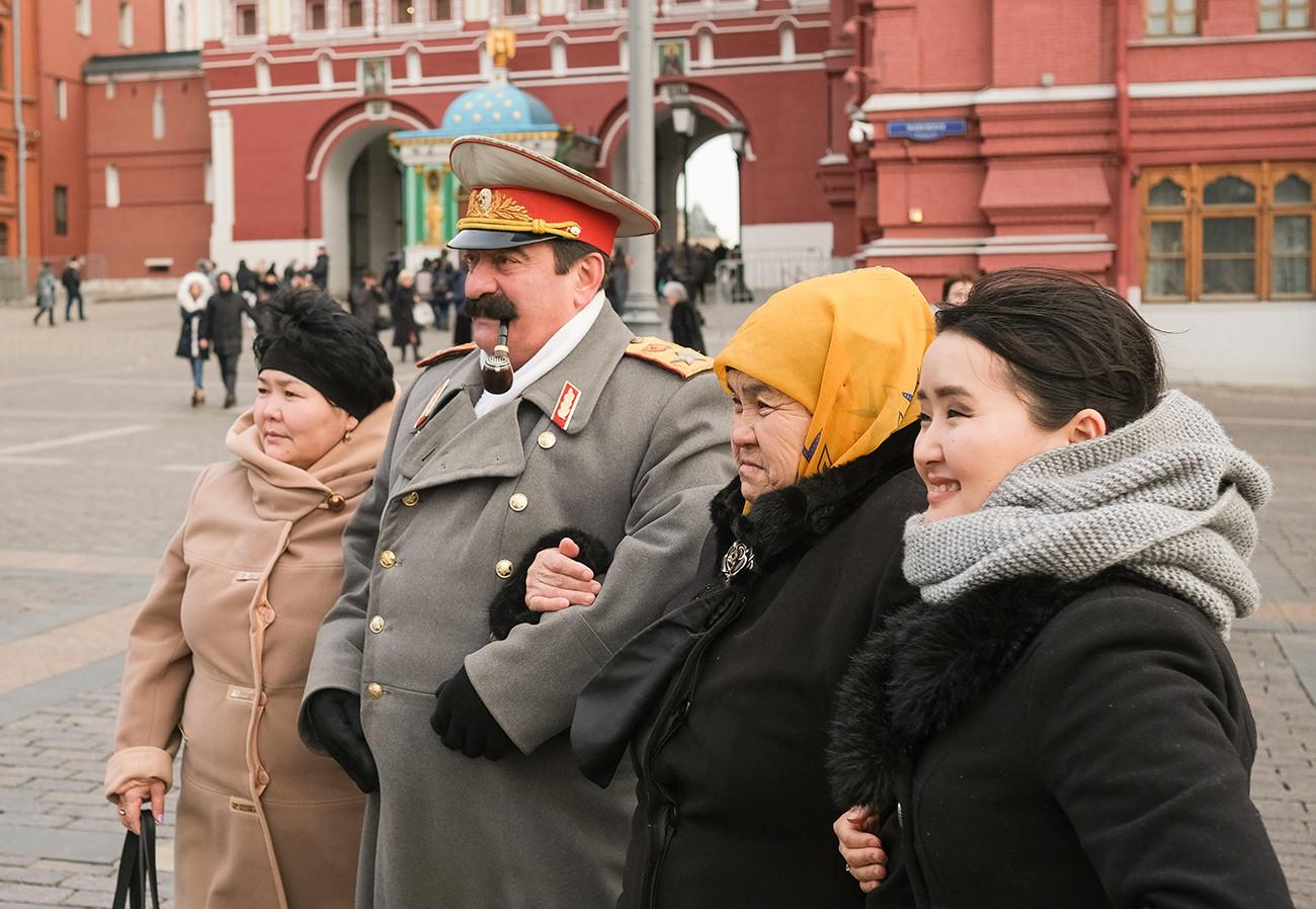 Туристы фотографируются с двойником Сталина на Манежной площади.