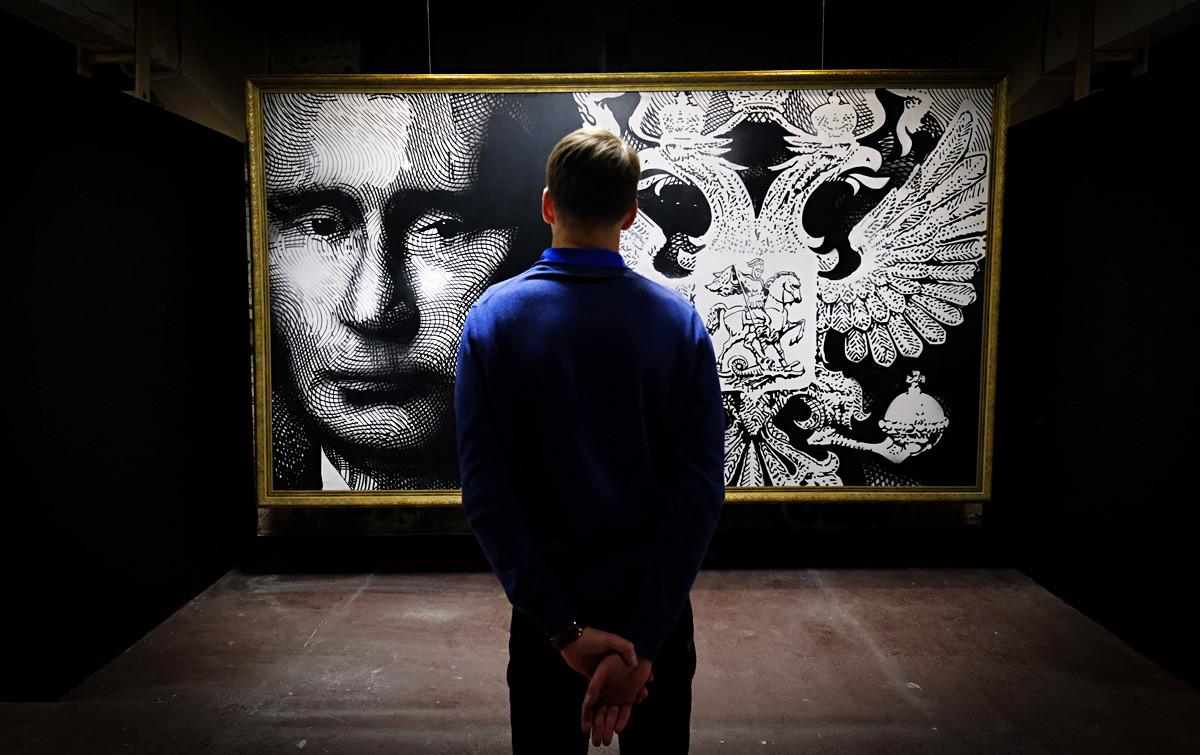 Čovjek promatra sliku koja prikazuje ruskog predsjednika Vladimira Putina na izložbi