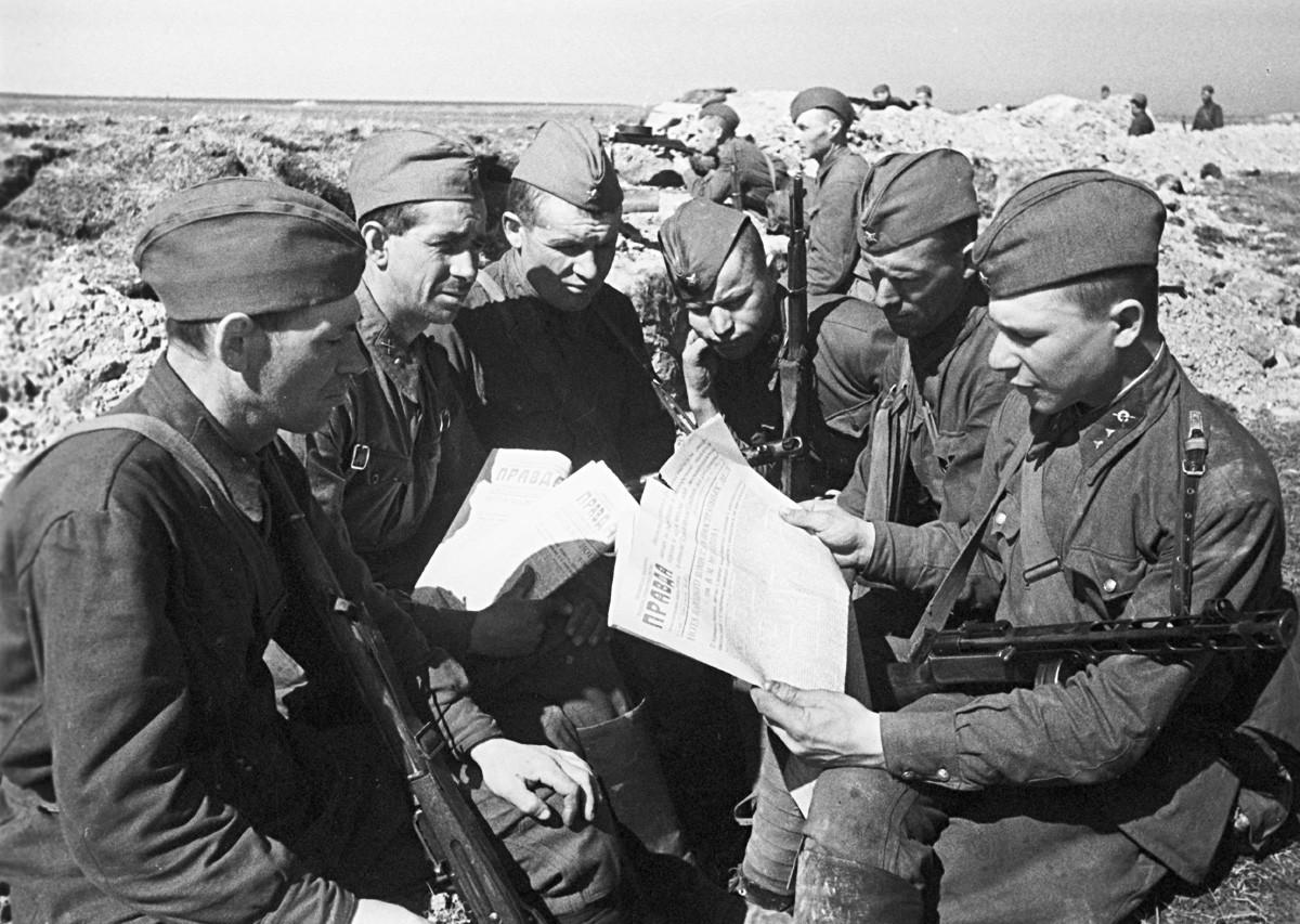 Soldados do Exército Vermelho lendo Pravda nas trincheiras em 1942, durante a Grande Guerra Patriótica