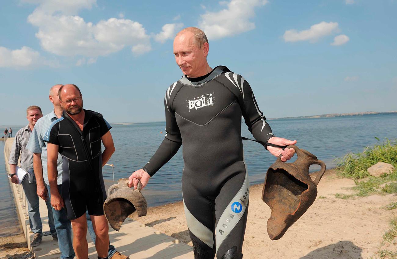 Vladimir Putin membawa pecahan amphora (sejenis wadah keramik berbentuk vas dengan dua pegangan dan bagian leher yang panjang) Yunani kuno setelah menyelam di Teluk Taman.