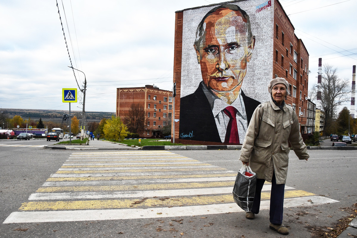 Anciana cruza la carretera frente a un mural de Putin en Kashira, pueblo situado a 115 km al sureste de Moscú. 16 de octubre de 2017.