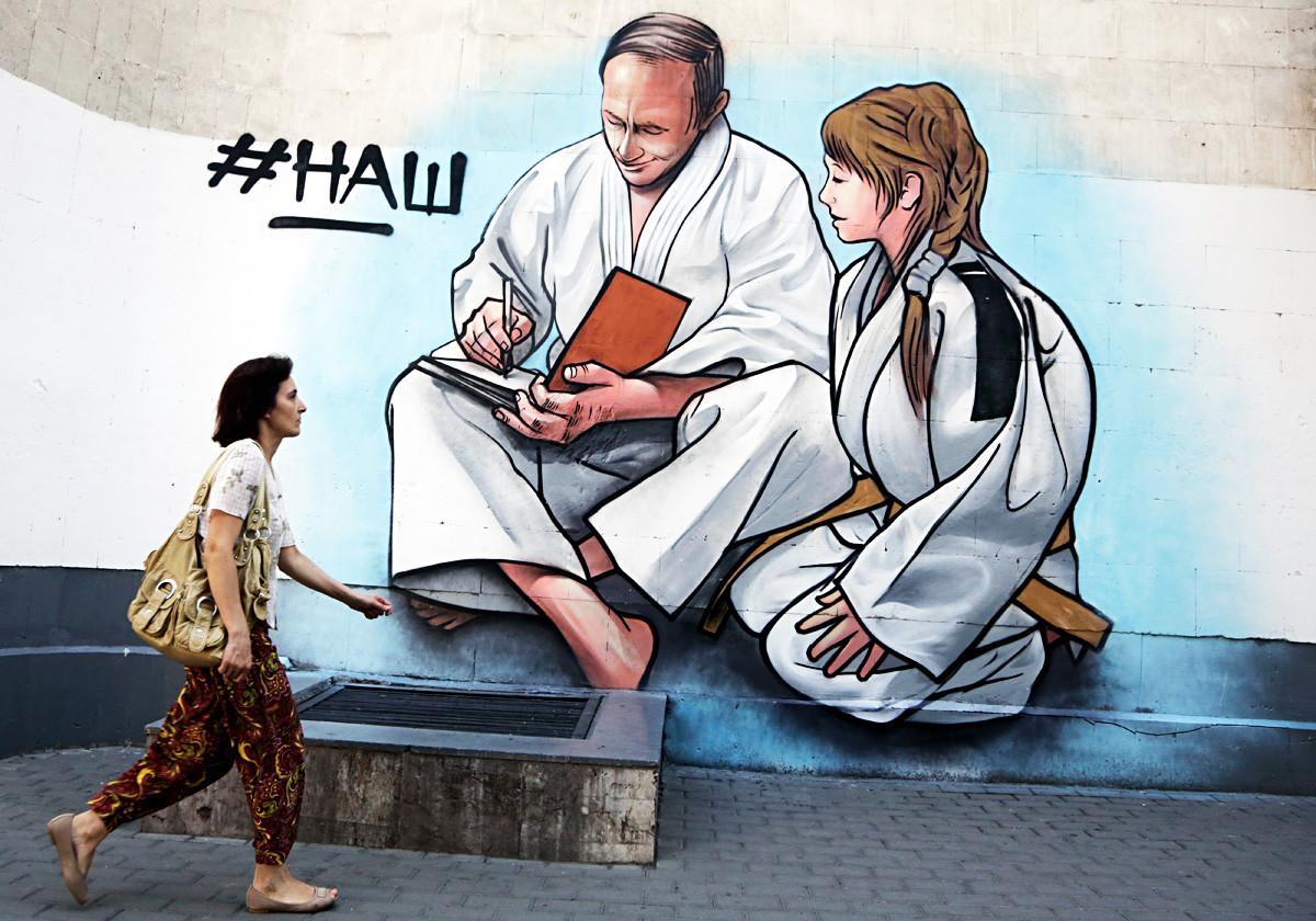 Mujer pasea frente a un grafiti de Putin, representado con un kimono de judo, en la ciudad crimea de Yalta.