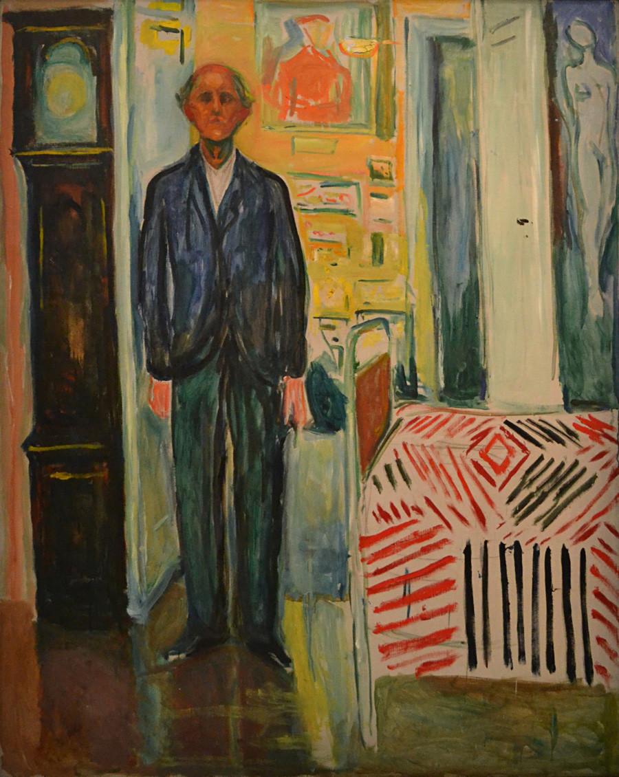 エドヴァルド・ムンク。『柱時計とベッドの間の自画像』1940-1943。