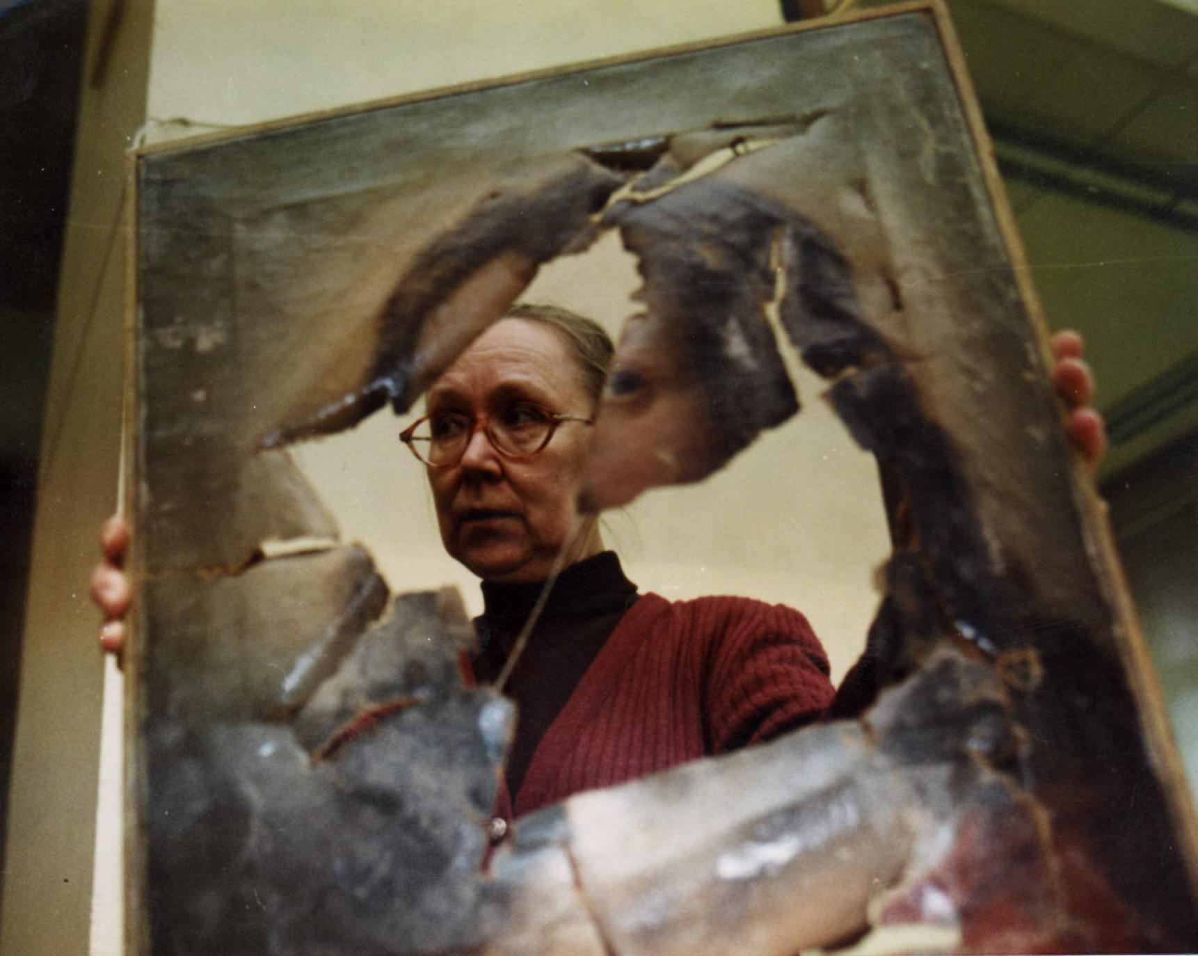 La restauratrice N. Kochkina et une toile abîmée pendant les guerres de Tchétchénie.