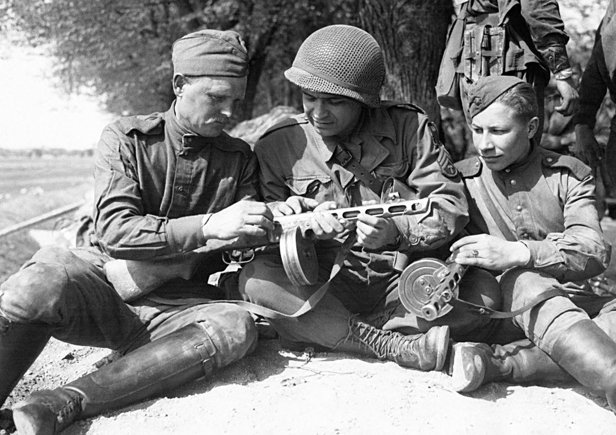 Амерички војник у друштву двојице руских војника упоређује наоружање после сусрета руских и америчких трупа на обали Елбе, Торгау, Немачка, 27. април 1945.