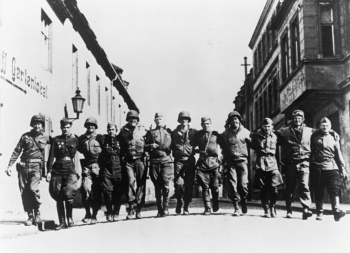 Насмејани амерички и руски војници загрљени ходају улицом на обали Елбе, Немачка, Други светски рат, 1945.