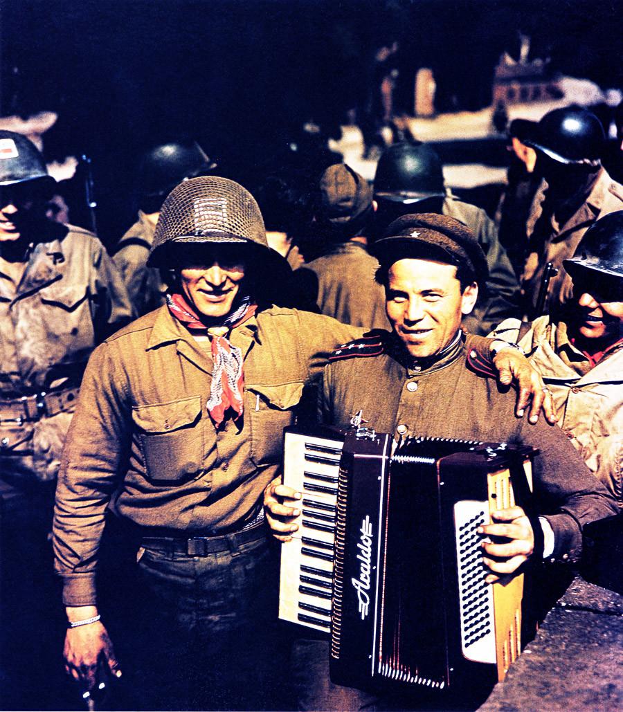 Руски војник са хармоником позира са америчким војником за време сусрета америчке и совјетске армије у граду Торгау 25. априла 1945. Америчка 69. пешадијска дивизија је срела совјетску патролу код реке Елбе јужно од града Торгау. Ово је био први такав сусрет на немачком фронту.