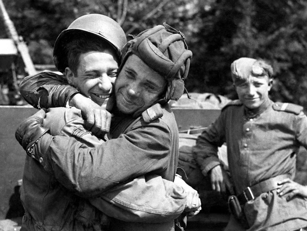 На овом снимку, који је ставила на располагање армија САД, руски војник (десно) грли фотографа 82. падобранске дивизије САД која је била придодата Другој британској армији, мај 1945. године, Грабов, Немачка.