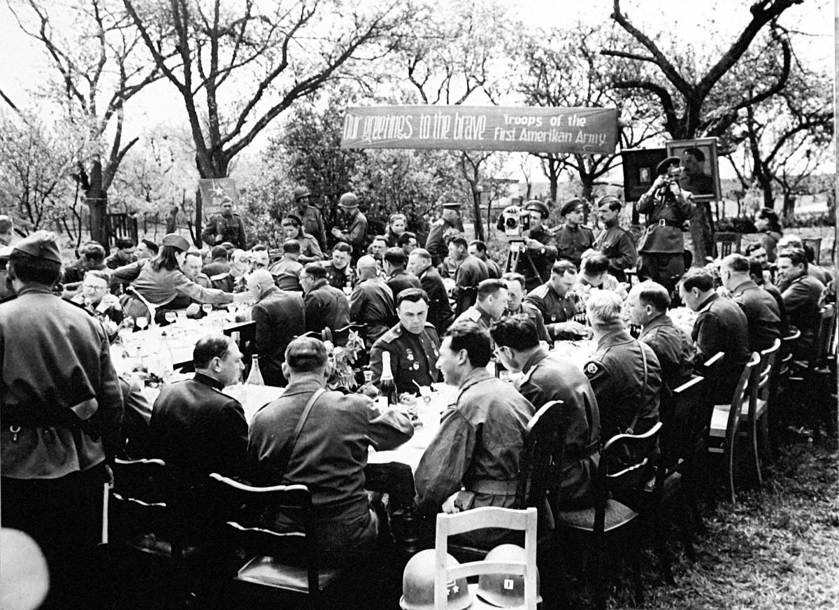 Ručak na otvorenom 27. travnja 1945. godine u čast zapovjednika američkih i sovjetskih trupa koje su se sastale na rijeci Elbi (Torgau, Njemačka) 25. travnja 1945. godine. U pozadini fotografija lidera Rusije Josifa Staljina i predsjednika SAD-a F. D. Roosevelta.