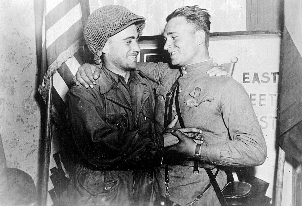 Nasmijani poručnik William Robertson i poručnik Crvene armije Aleksandar Siljvaško ispred natpisa [Istok susreće Zapad] postali su simbol povijesnog susreta sovjetske i američke vojske blizu grada Torgaua, Njemačka.