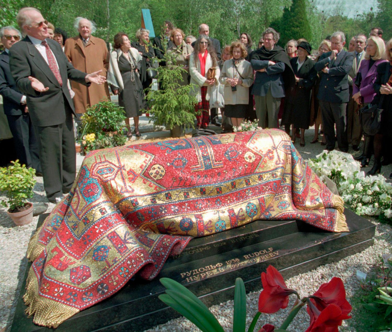 ルドルフ・ヌレエフ基金の会長がヌレエフの墓を飾る新しい石碑を見せる。1996年5月6日、サント=ジェヌヴィエーヴ=デ=ボワの「ロシア人墓地」にて。