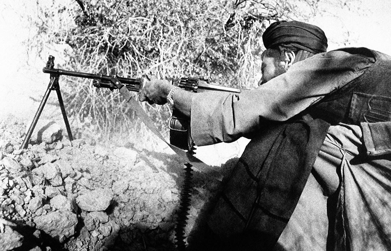 Mudžahedin, oborožen z mitraljezom kalibra 7,62 mm med urbanim spopadom s sovjetsko vojsko v drugem največjem afganistanskem mestu Kandahar. Do končnega sovjetskega umika so afganistanske gverilske skupine postopoma vse bolj napredovale. V spopadih je bilo uničenih 70 odstotkov mesta.