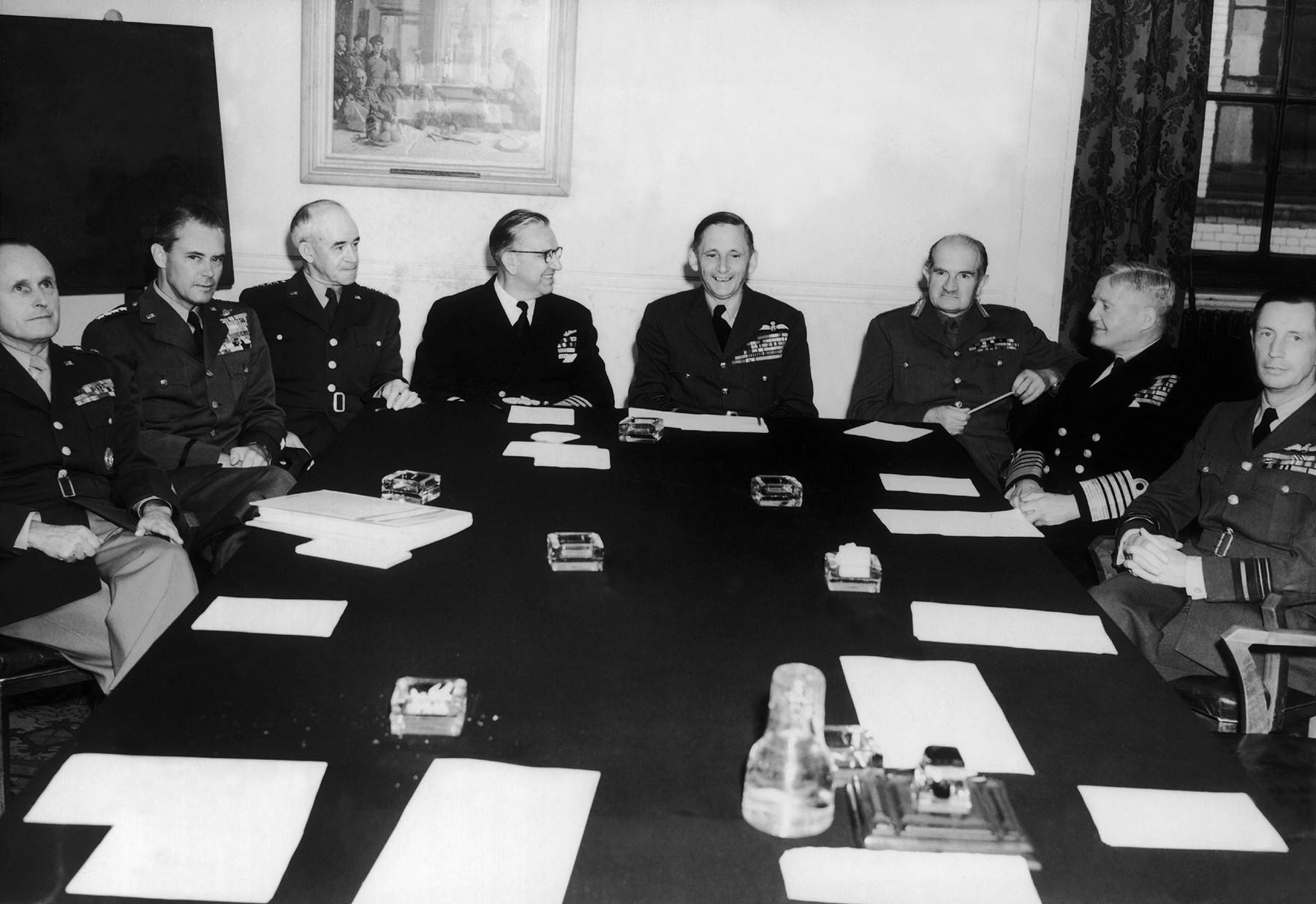 Autour de la table des négociations à Londres. De gauche à droite : le général-major Alfred M. Gruenther; le général Hoyst S. Vandenberg; le général Omar N. Bradley: l'Amiral Louis E. Denfield; le lord Tedder; le maréchal William Slim; l'amiral Fraser et le maréchal William Elliot.
