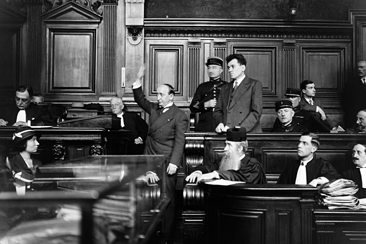 Pariz, Francuska 25. srpnja 1932. Pavel Gorgulov, ubojica francuskog predsjednika Paola Doumera, na optuženičkoj klupi sa svojim odvjetnikom i svjedokom koji polaže prisegu prije davanja izjave.