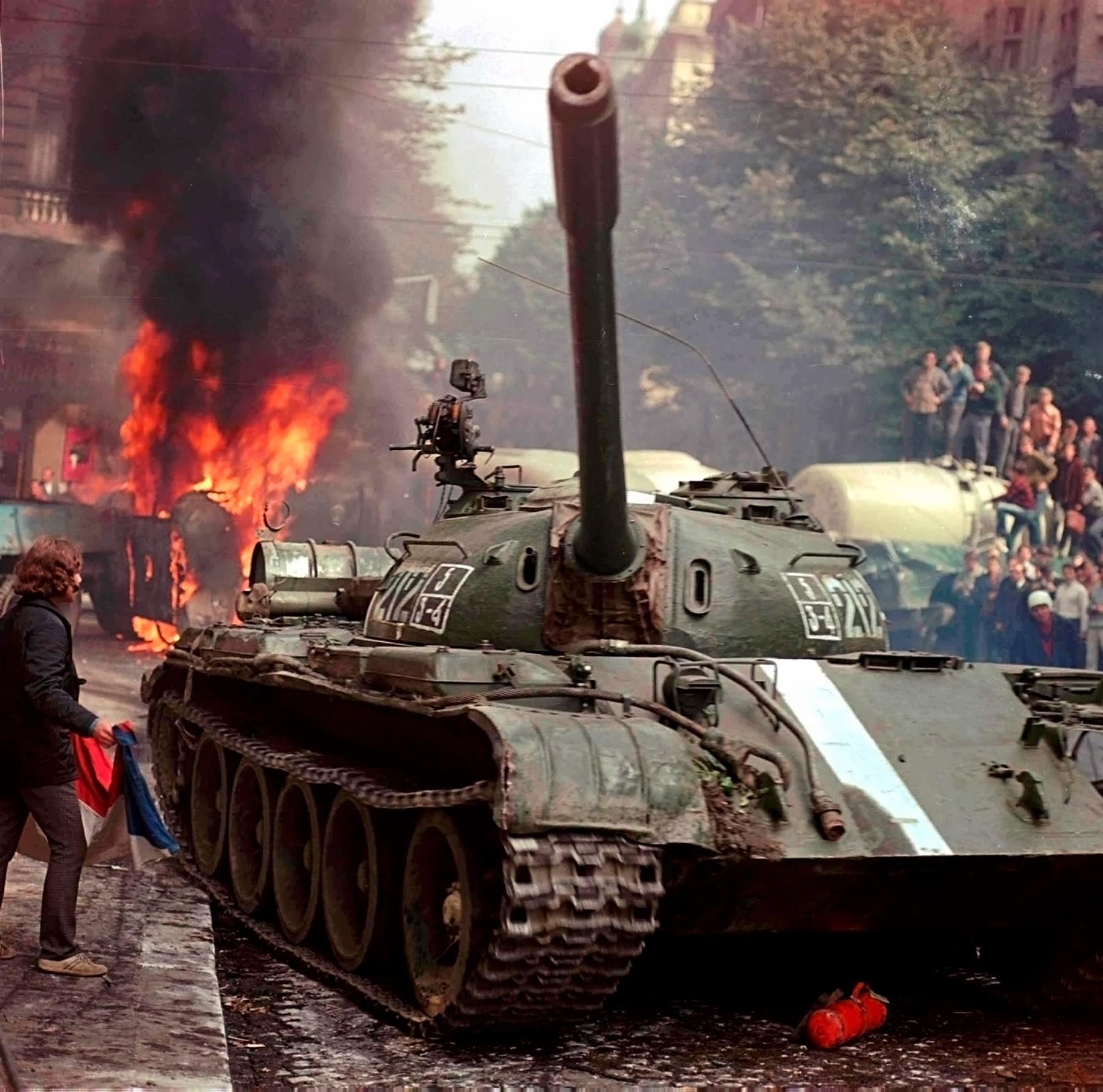1968年8月。チェコスロバキアのラジオ、プラハ本局付近で間に合わせのバリケードを通ろうとしているソ連の戦車。