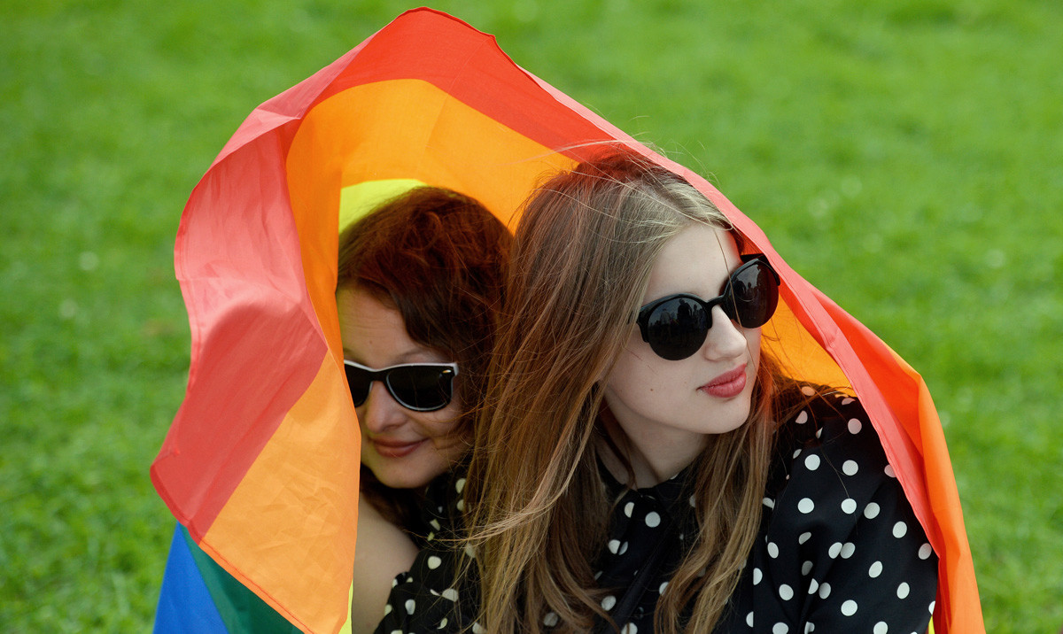 Activists shelter under a gay rights' movement rainbow flag during the gay pride rally in Saint Petersburg in 2017.