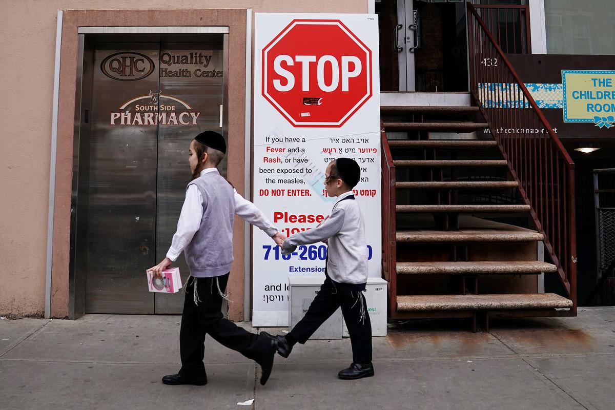 25 април 2019 г., Ню Йорк, САЩ. Деца до предупредителния знак за множество заболели от едра шарка в Бруклин.